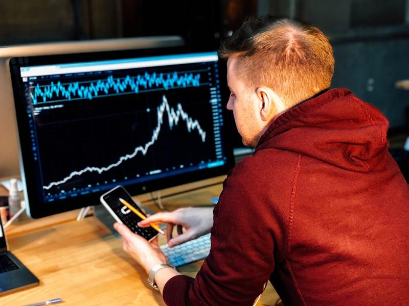パソコンで株価チャートを見る男
