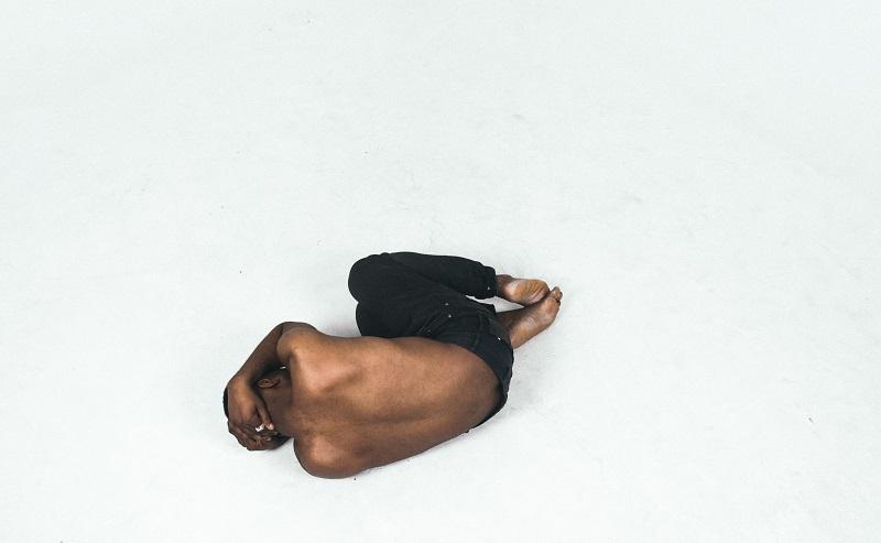 裸で頭を抱えて寝転がる男