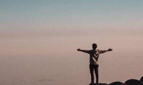 自由山の頂上で両手を広げる男