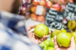 2つのリンゴを比べる男性