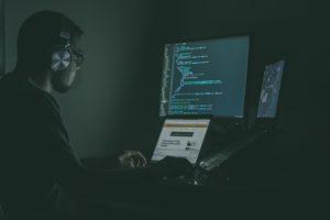 暗闇でパソコンに向かって作業する男 ネットでの詐欺のイメージ
