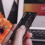 パソコンの前でクレジットカードを持つ手