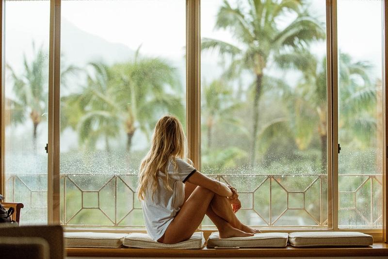 窓の外の天気を見て様子をうかがう女性