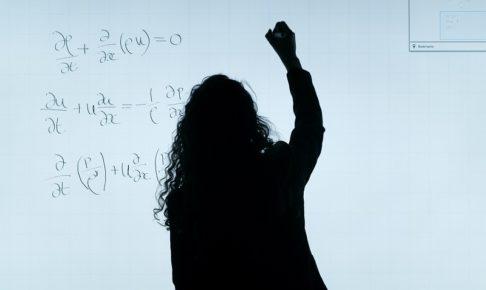 黒板で計算する女性で投資効果の計算をイメージ