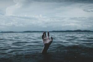 会社を辞められないイメージを水面に出た手で表現
